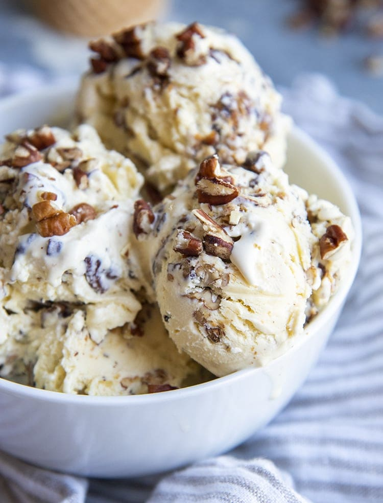 A close up of a bowl of butter pecan ice cream topped with sprinkles of chopped pecans.