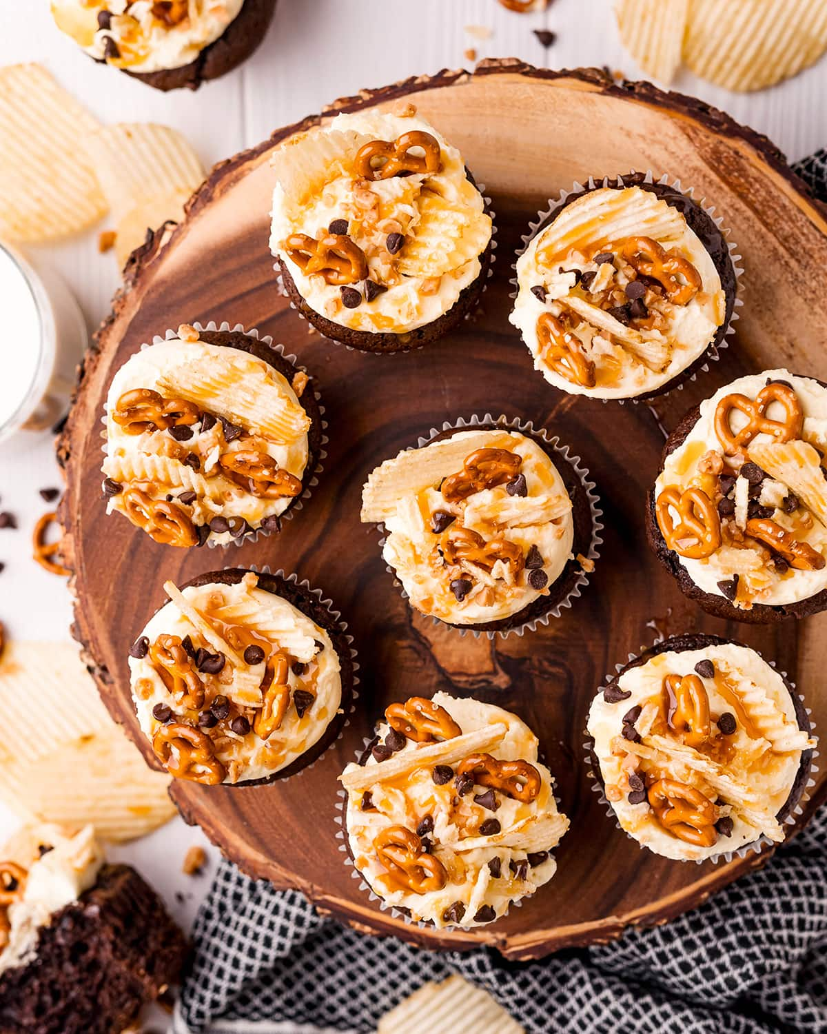 Chocolate cupcakes on a wooden stand topped with mini pretzels, ruffle chips, chocolate chips, and toffee pieces.