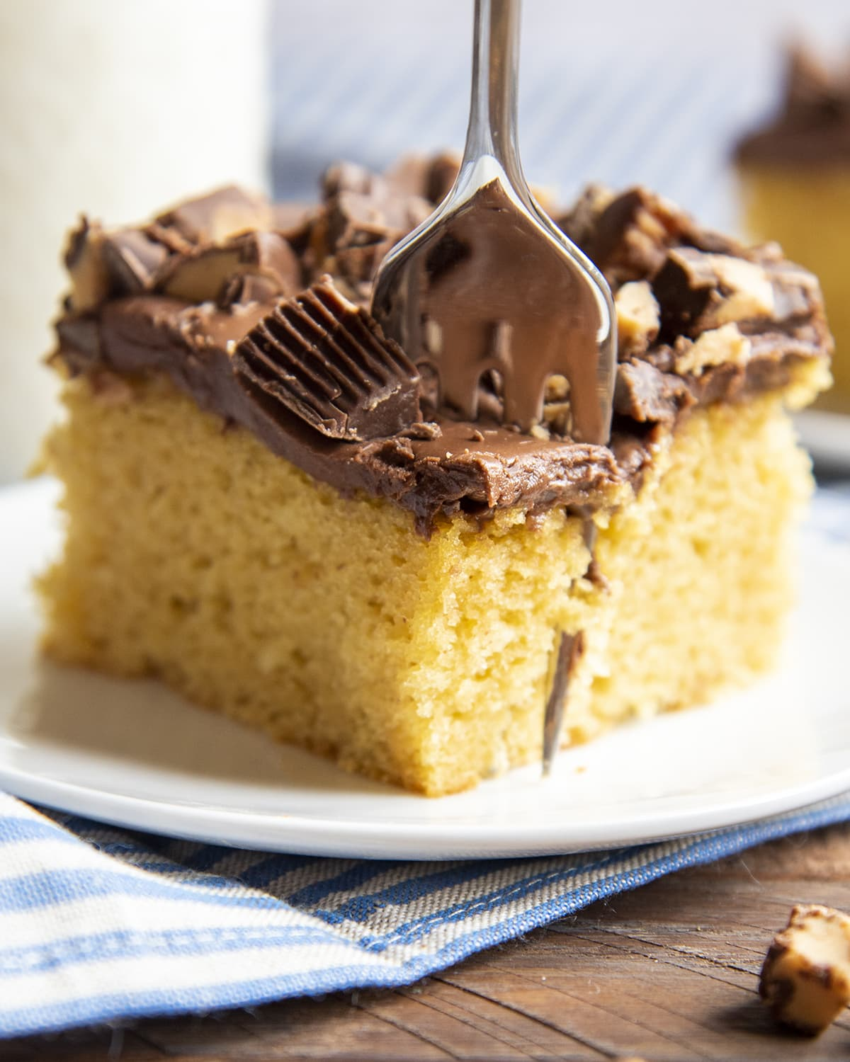 A piece of peanut butter cake with a cake mix topped with chocolate frosting and peanut butter cups. With a fork in the cake cutting out a bite.