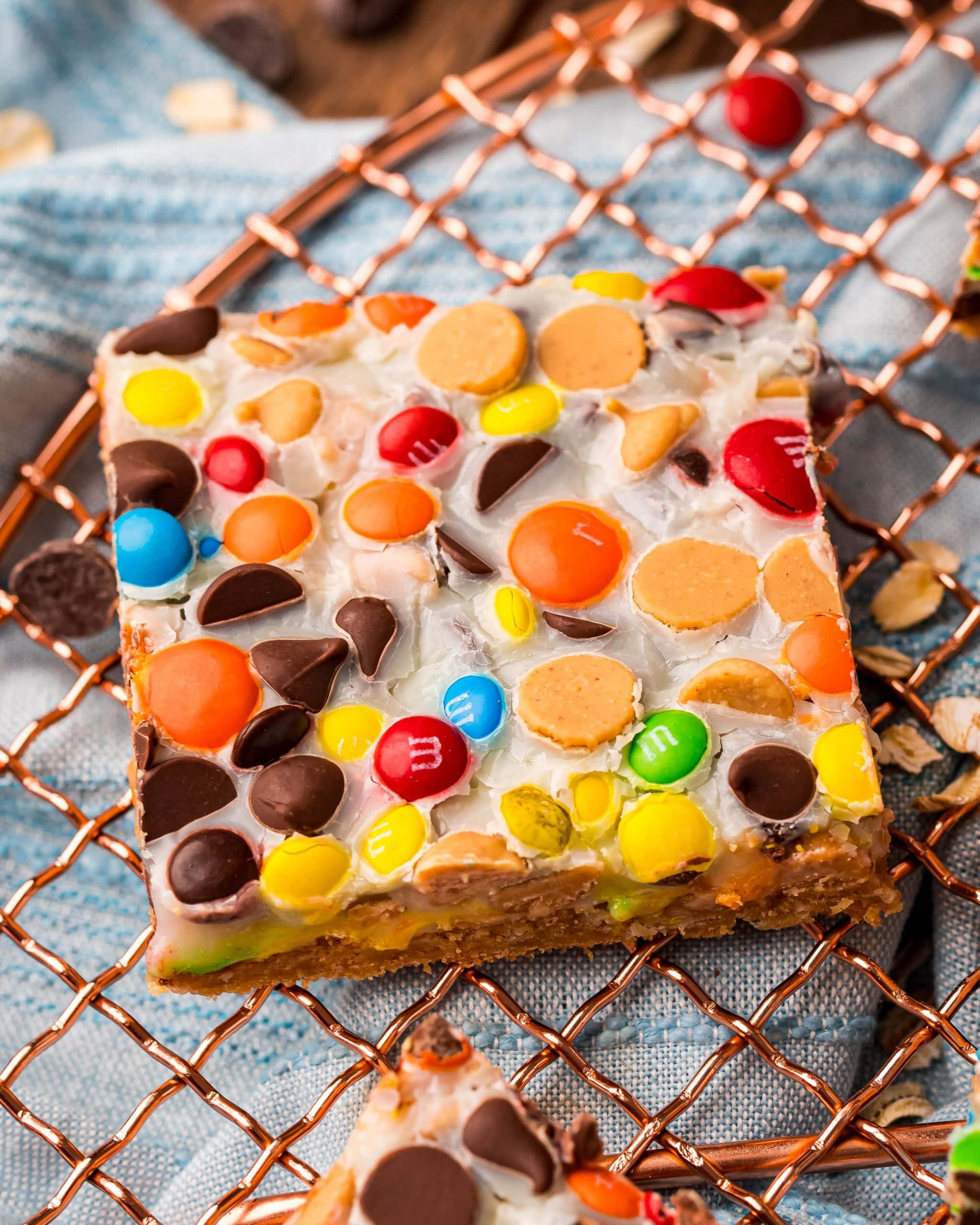 A close up of a monster cookie magic bar on a wire rack, with a variety of m&m colors, chocolate chips, and peanut butter chips in a white sweetened condensed milk layer.