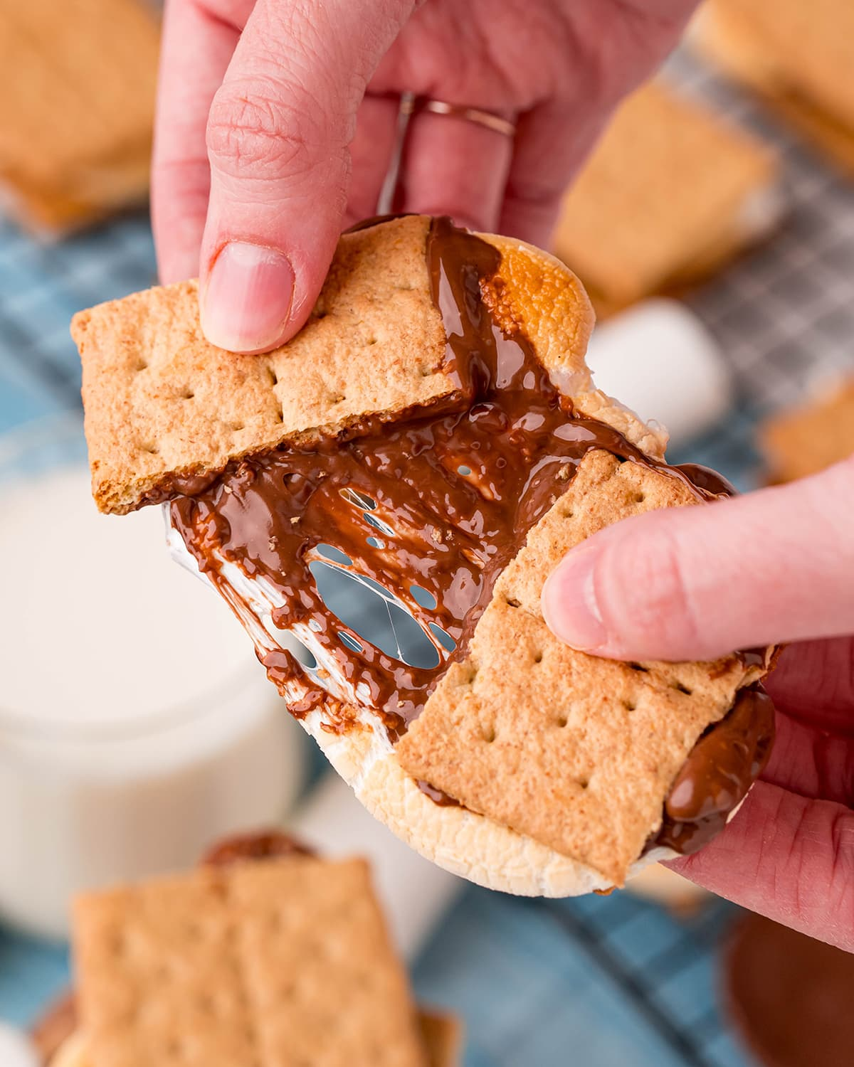 A hand holding a s'more, broken in half showing the gooey marshmallow and chocolate separating in the middle.