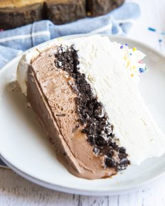 A slice of ice cream cake laying on a plate, the bottom half is chocolate, with a layer of oreo crumbs, then vanilla ice cream, and topped with whipped cream and a whipped rosette.
