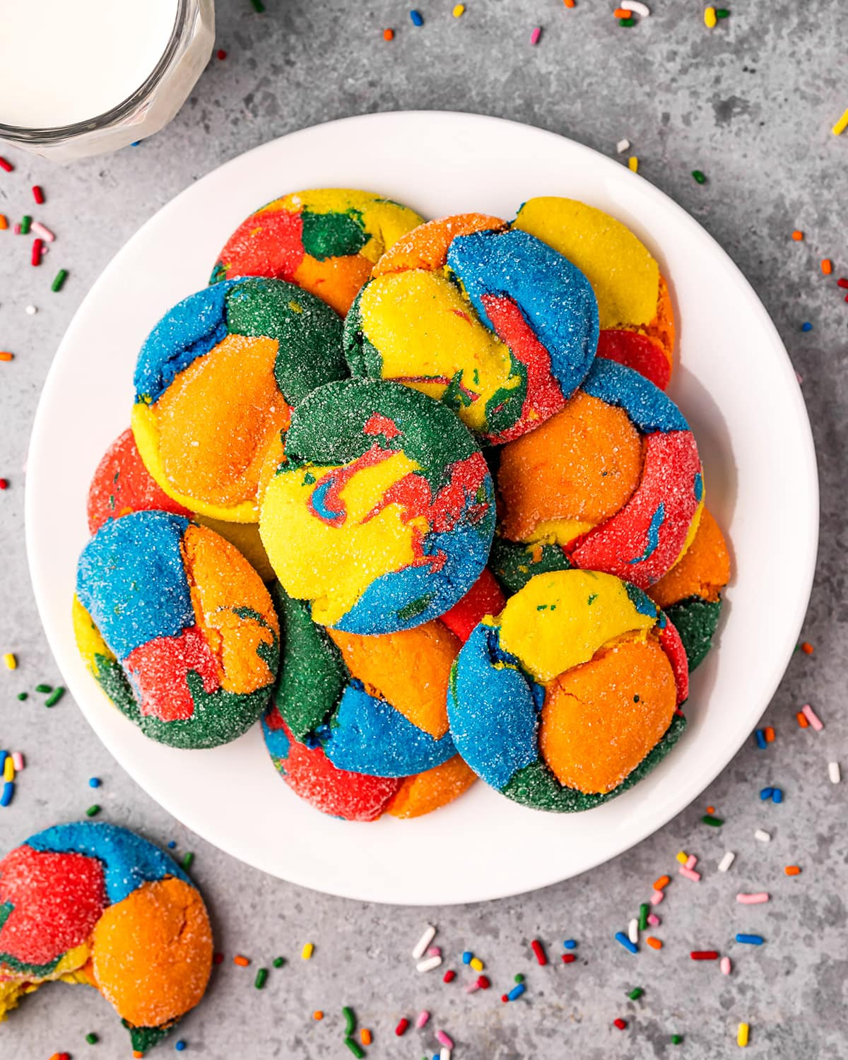 A pile of rainbow cake mix cookies. The cookies are swirled with red, orange, yellow, green, and blue colors, and you can see granulated sugar on them.