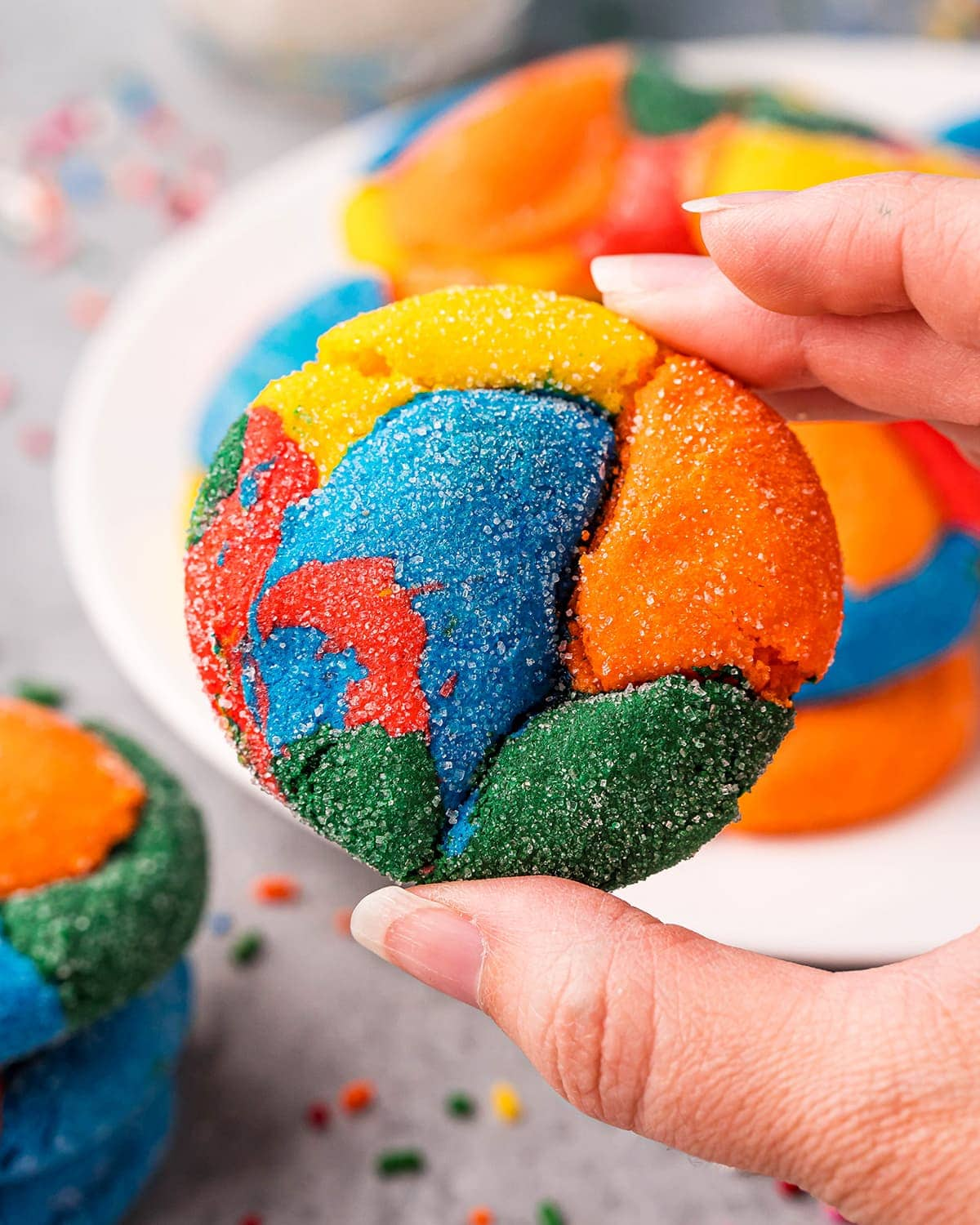 A hand holding a rainbow swirled cookie, with red, yellow, orange, blue and green colors.