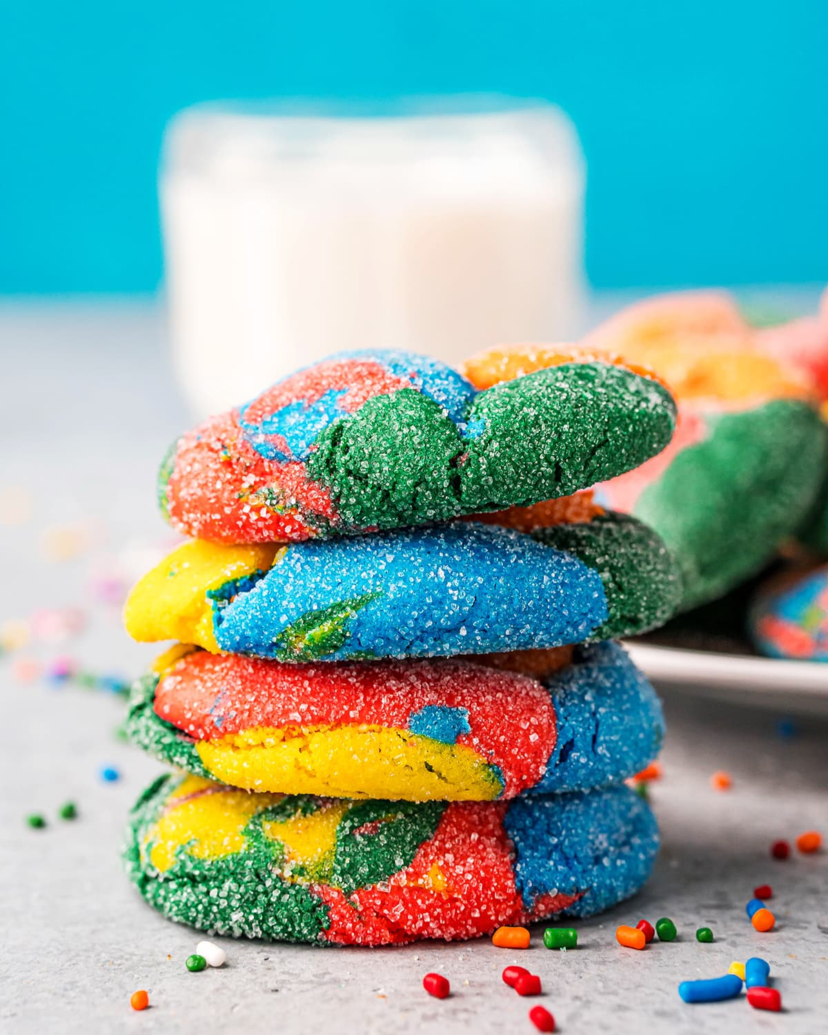 A stack of 4 puffy, rainbow colored cookies.