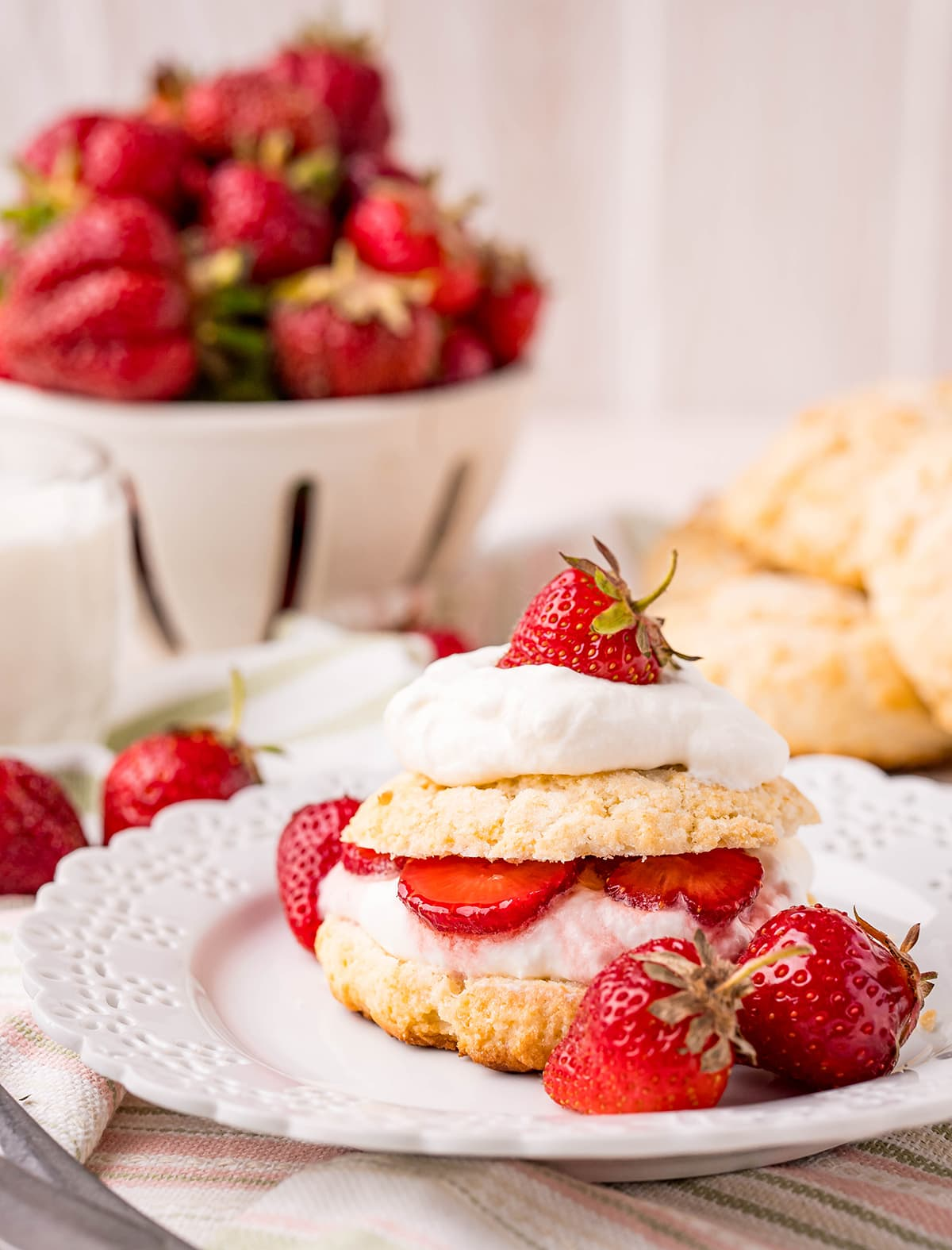 A strawberry shortcake on a plate, with a sweet biscuit, whipped cream, and strawberries. With a bowl of strawberries in the back, and a pile of biscuits.