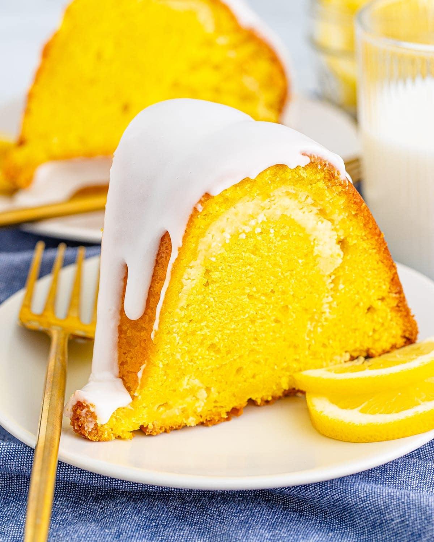 A slice of lemon bundt cake with glaze on a white plate.