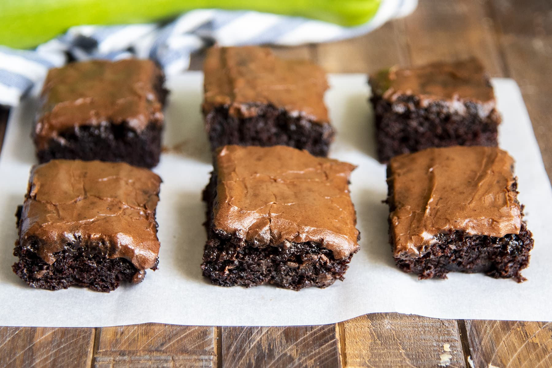 Six frosted brownies on a piece of parchment paper.