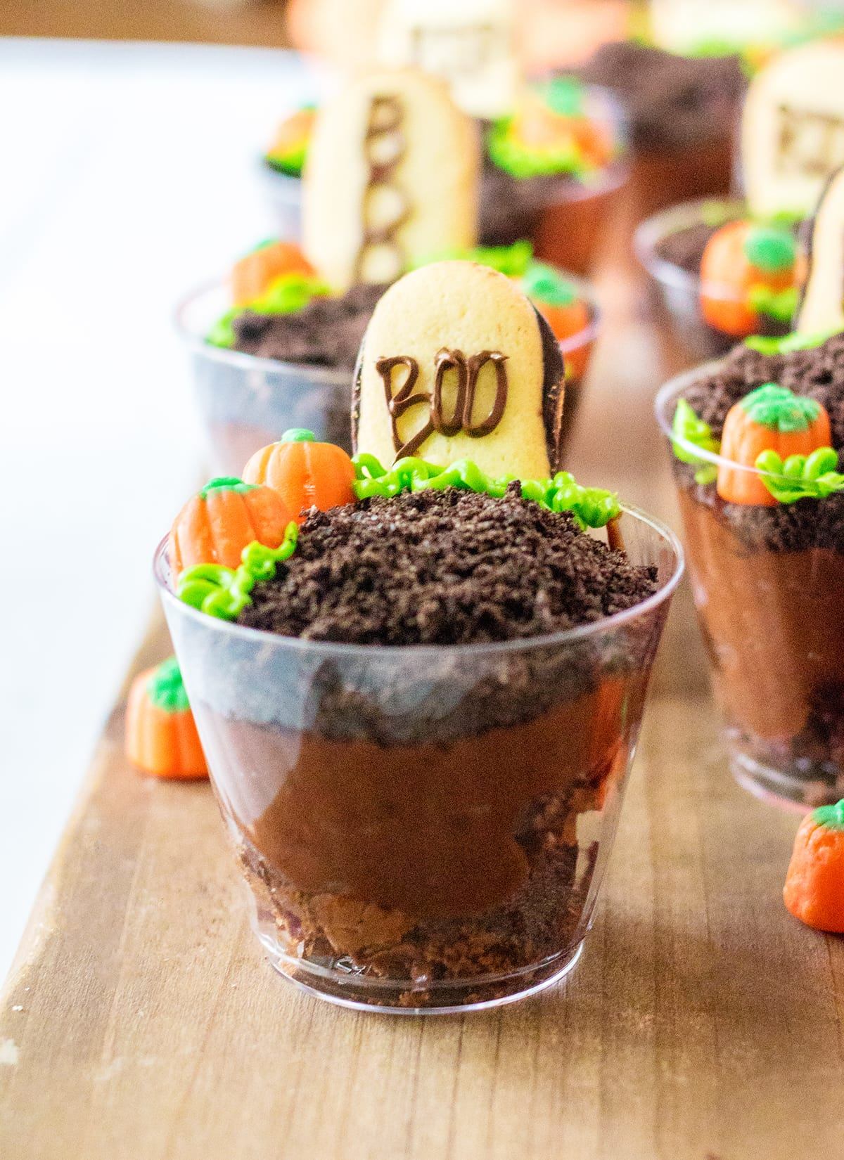 A line of graveyard pudding cups topped with cookie tombstones saying BOO.