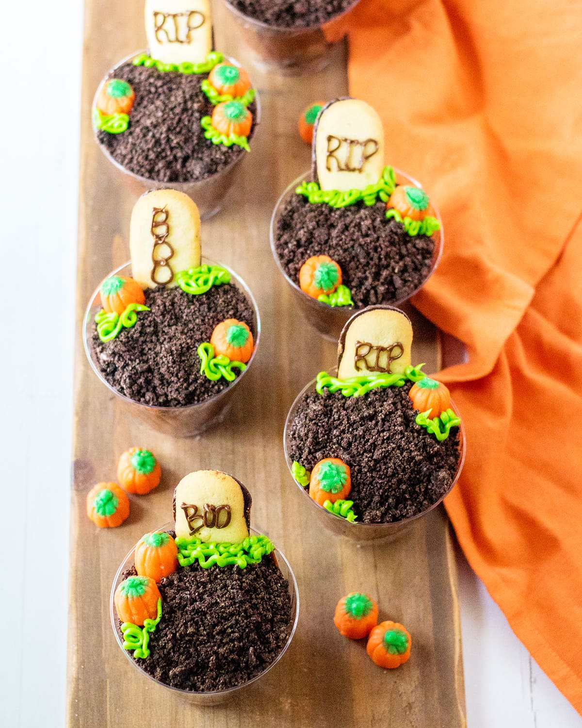 An overhead shot of graveyard pudding cups topped with Oreo crumbs and cookie tombstones.