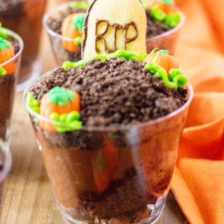 """A close up of a graveyard pudding cup topped with chocolate cookie crumbs and a cookie """"tombstone"""" saying RIP."""