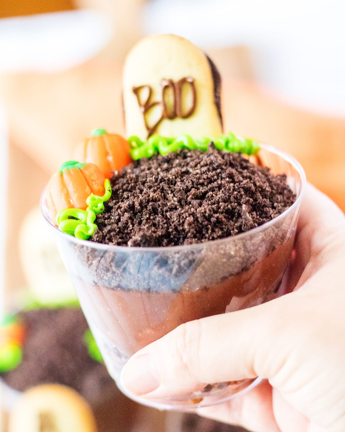 """A hand holding a halloween pudding cup with pudding, and Oreo crumbs. Topped with candy pumpkins and a cookie that says """"boo"""" on it."""