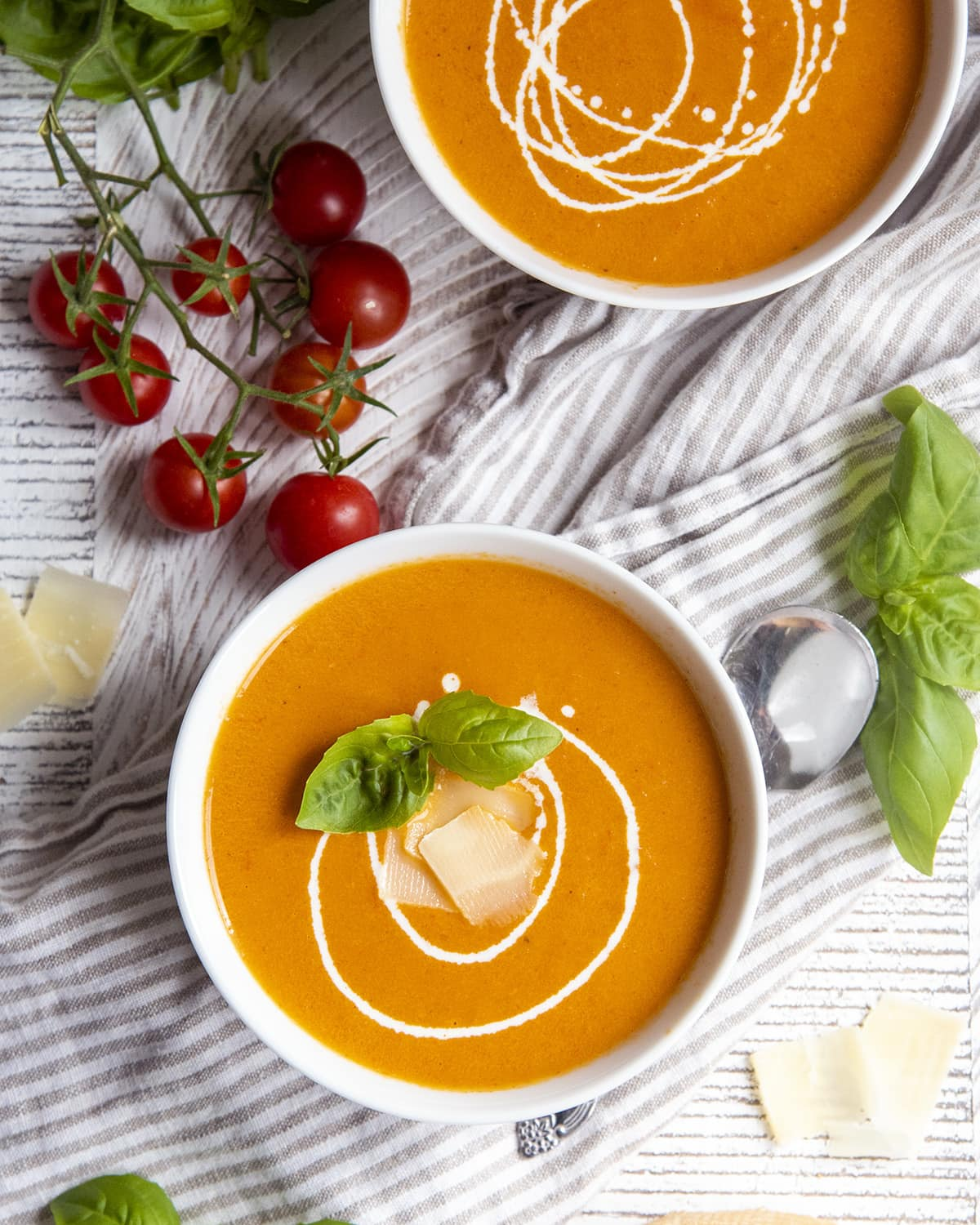 An overhead shot of two bowls of tomato basil soup.