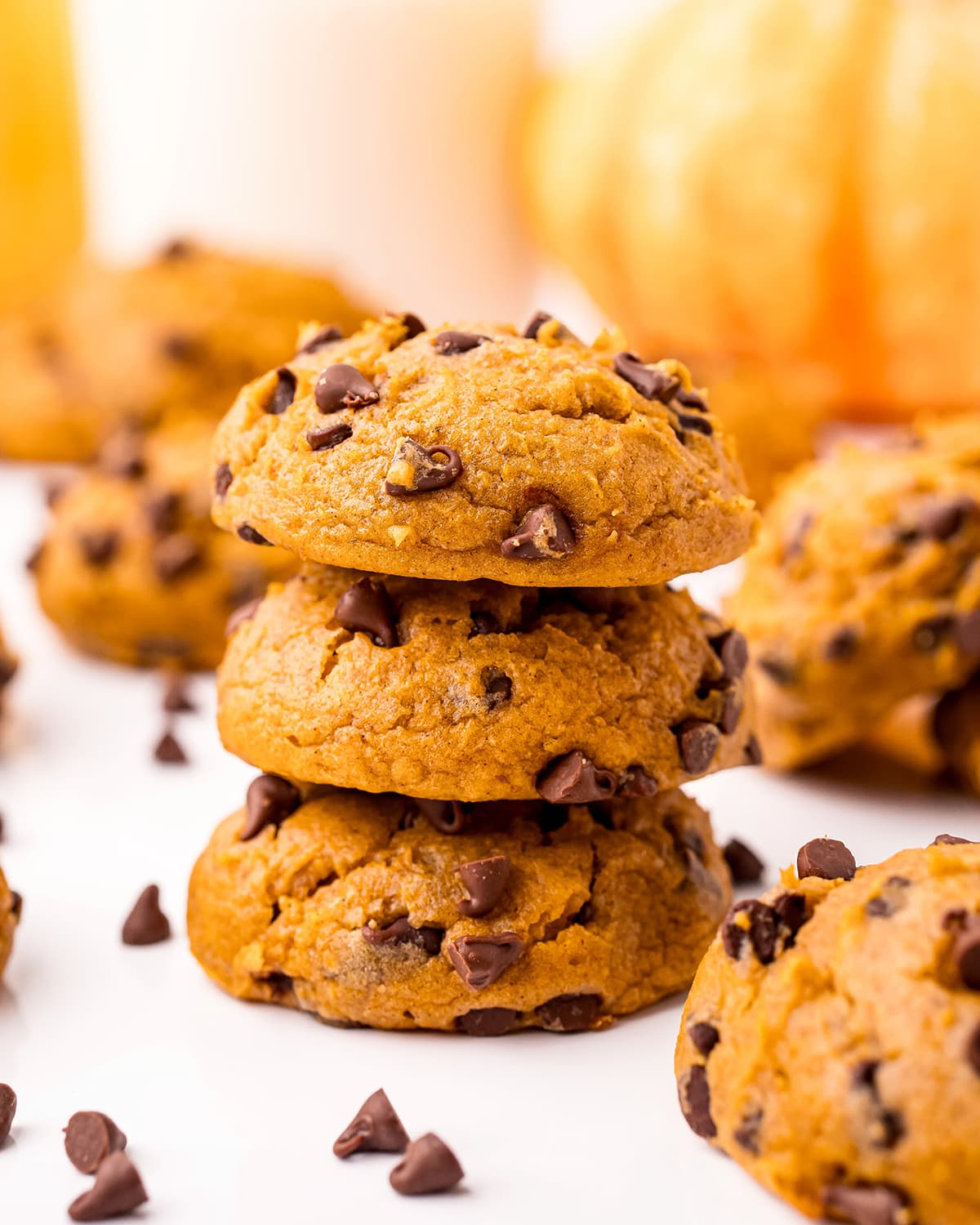 A stack of three pumpkin chocolate chip cookies with other cookies around it.