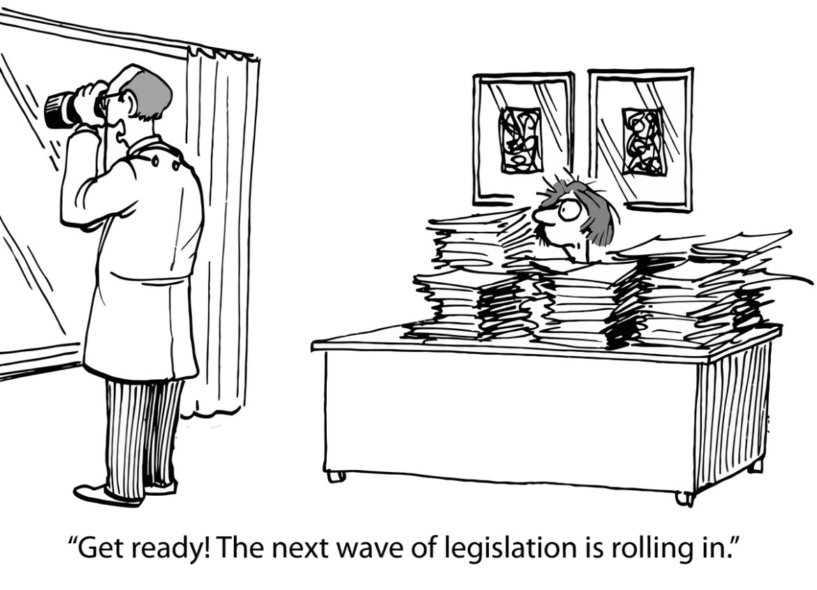"""Guy looking out window with binoculars. Woman at desk covered in files. Caption: """"Get ready! The next wave of legislation is rolling in."""""""