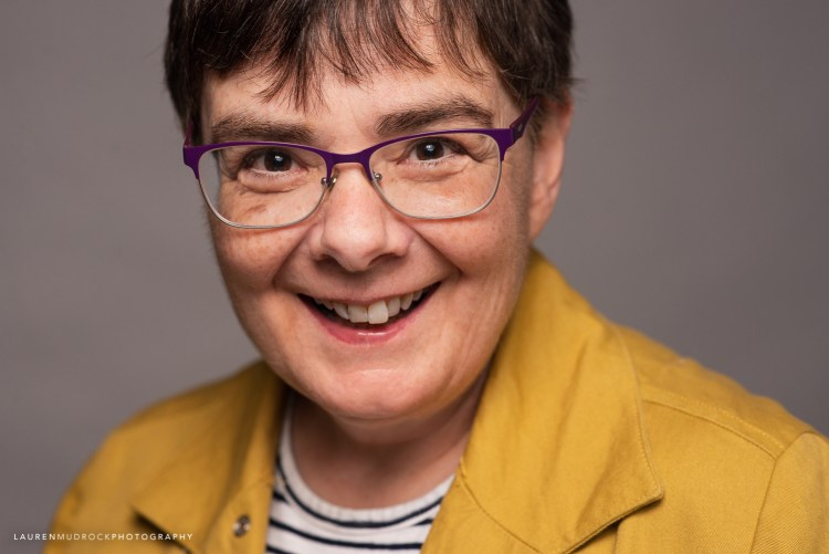 yellow jacket purple glasses studio headshot