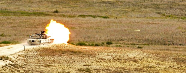 """An M1A2 Abrams tank crew from Company D, 1st Battalion, 12th Cavalry Regiment, 3rd Brigade Combat Team, 1st Cavalry Division fires the main gun during a Gunnery Table VI live-fire exercise at Blackwell Multiuse Range Sept. 16 at Fort Hood, Texas. Table VI is an annual qualification for the tank crews where many of the crews compete for """"Top Tank."""" (U.S. Army photo by Sgt. Kim Browne, 3rd BCT PAO, 1st Cavalry Division)"""