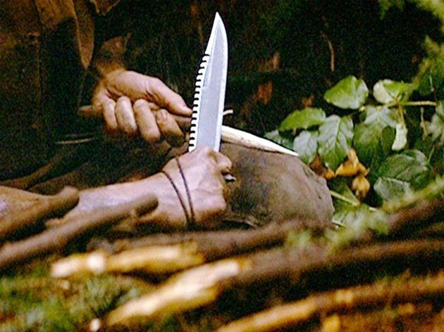 Sylvester Stallone as John Rambo sharpening a stick with a knife