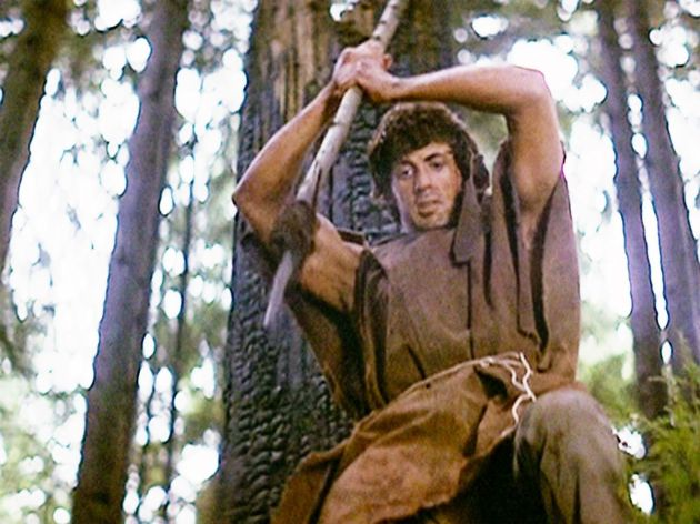 Sylvester Stallone as John Rambo about to spear a wild boar using his knife.