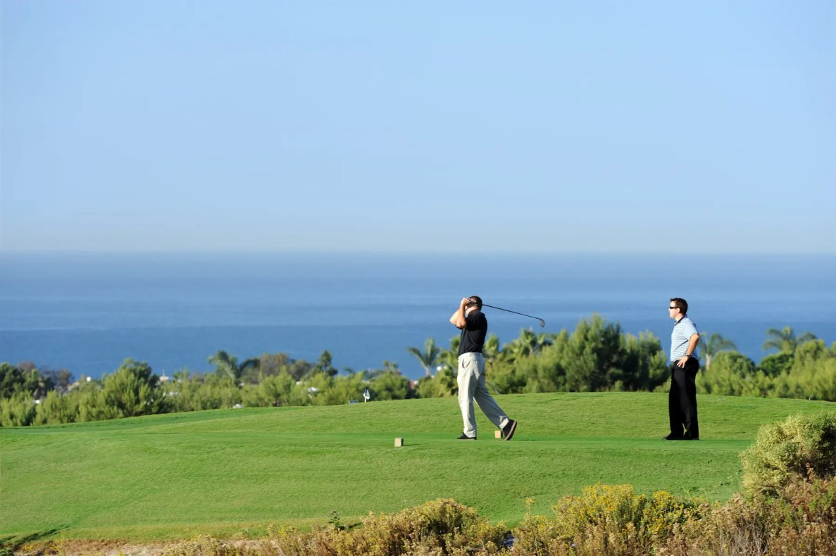 Golfers teeing off Hole #1, Par with the Pacific Ocean in the background.