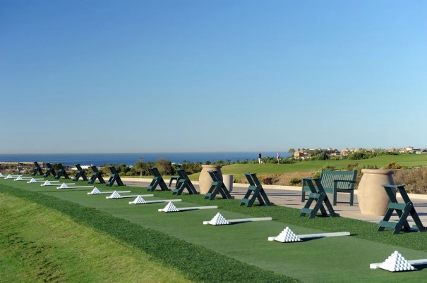Practice facility with golfers teeing off Hole #1, Par 4 Pacific Ocean in the background