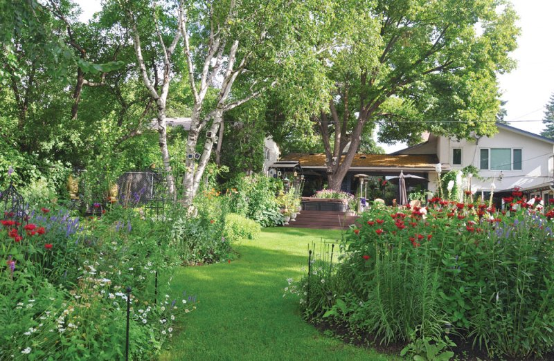 A lush green pathway leads from the house down to the river past centre island plantings