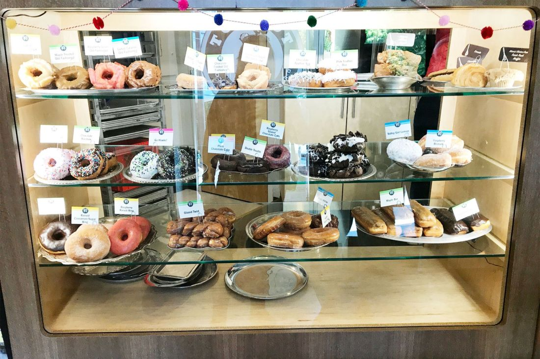 A glass showcase featuring stacks of colorful doughnuts