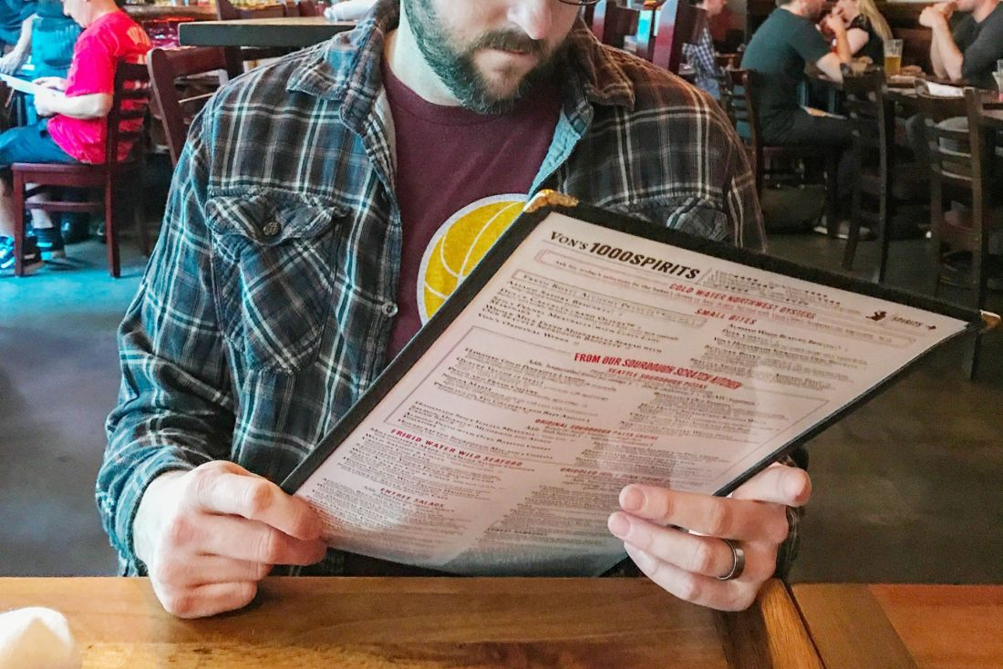 Man in flannel shirt reading menu at a restaurant
