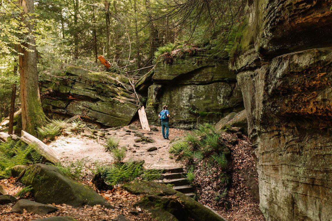 Man walking a trail along moss covered rocks