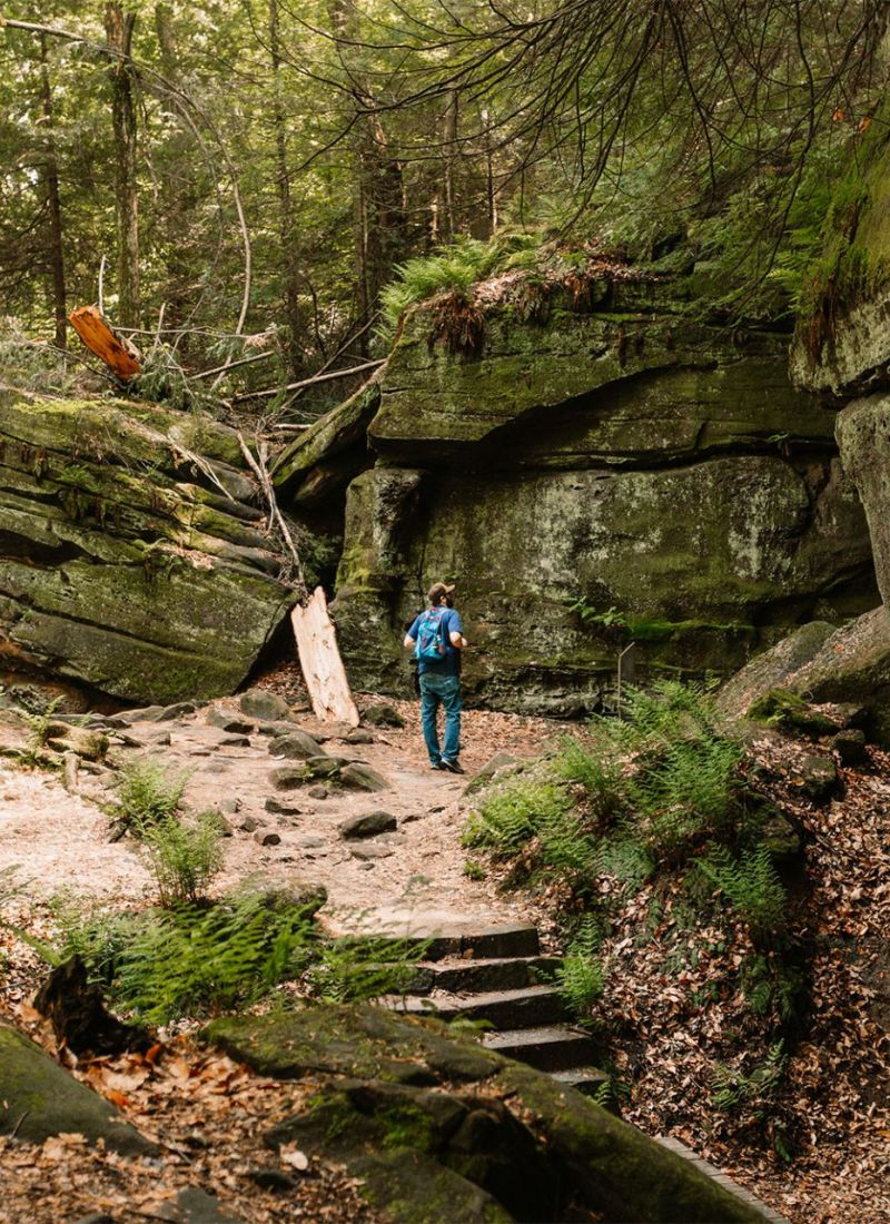 Man walking a trail along moss covered rocks