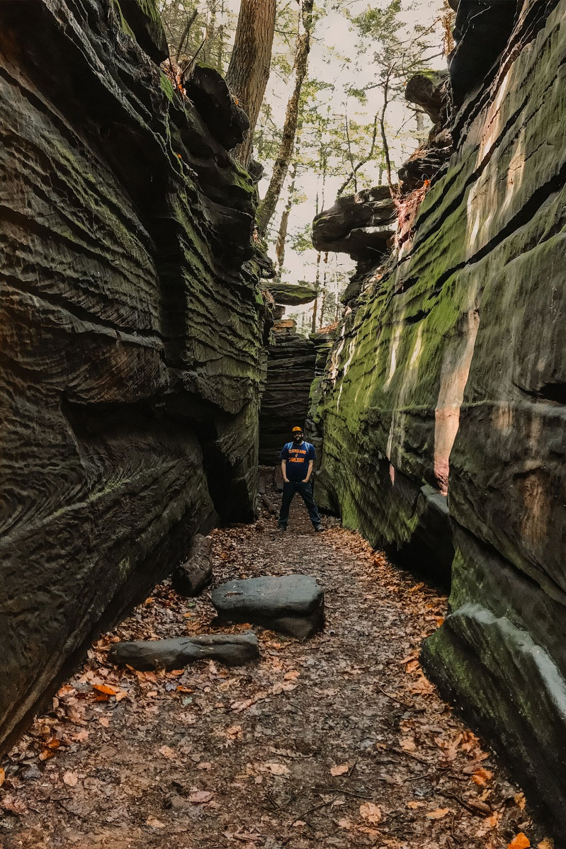 Man standing between moss covered rock formations