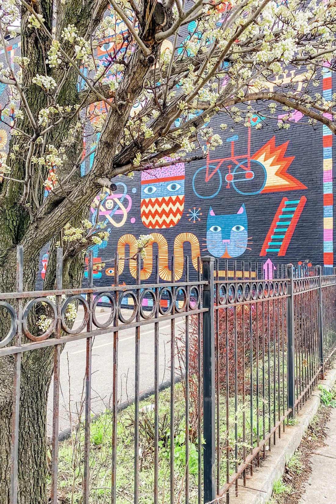 Colorful characters on brick wall behind fence and tree