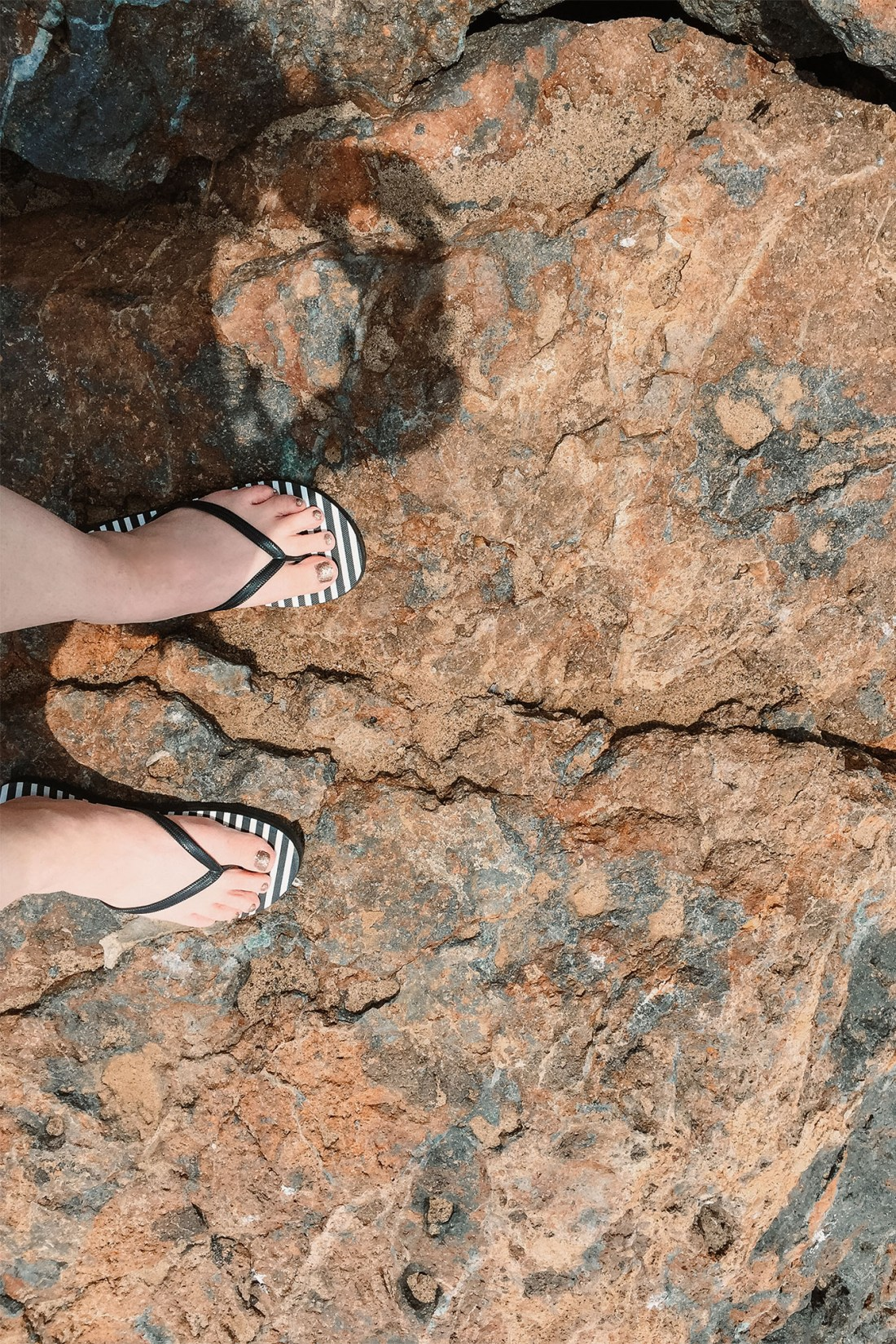 Femail in striped flip flops on rocky surface in Point Dume, Malubu | as seen on the Local Love and Wanderlust Blog