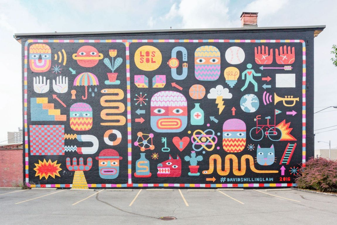 Colorful characters painted on brick wall