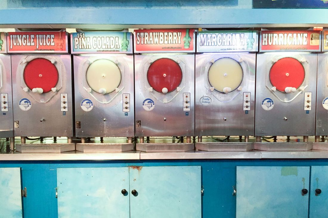Machines with colorful frozen drinks against blue wall