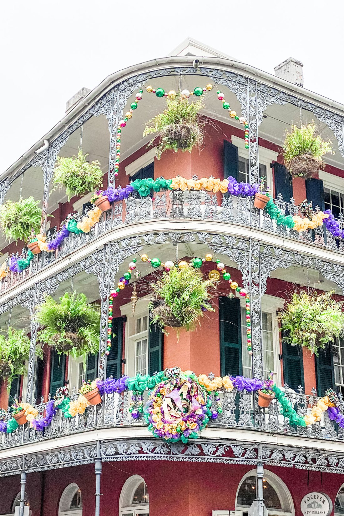 Brick building with wrought iron balcony and hanging plants in New Orleans