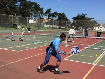 Pickleball is the fastest growing sport among seniors. McClaren Park is one of several places in San Francisco where the game can be played. Chen, in back, is getting a lesson from Jason Batong. (Photo by Freddie Nadarisay)