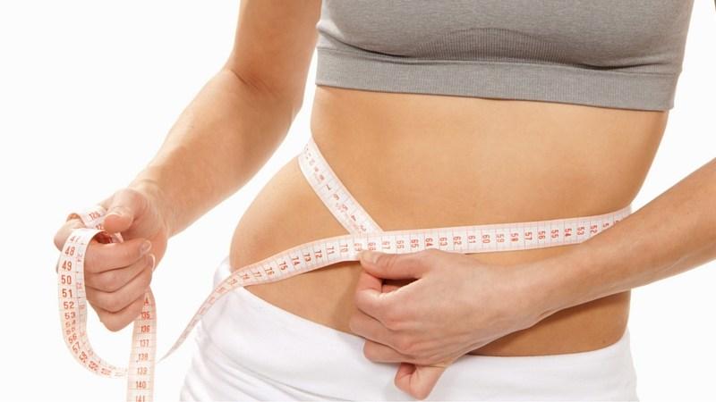 woman measuring her waist line