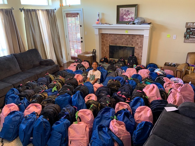 jaxson surrounded by backpacks he has donated