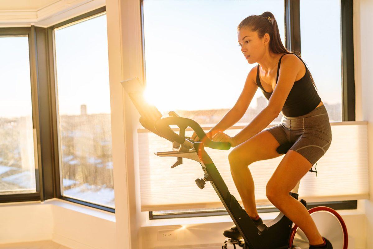 Girl rides a Peloton bike