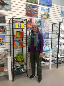 Artist Heather Richman next to her glass work. Heather, along with artist Nancy Moore, are AAR members who assist customers, organise merchandise, and support other participating artists.