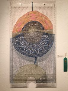 """Mercury Rising by Pam Moore. Knitted lace mounted on plexiglass frame. Honorable Mention."