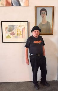 Artist and curator Frank Foreman under a self portrait by Judy Foreman.