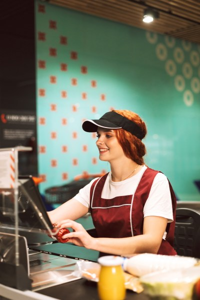 Young smiling female cashier in uniform joyfully using cashbox working in modern supermarket