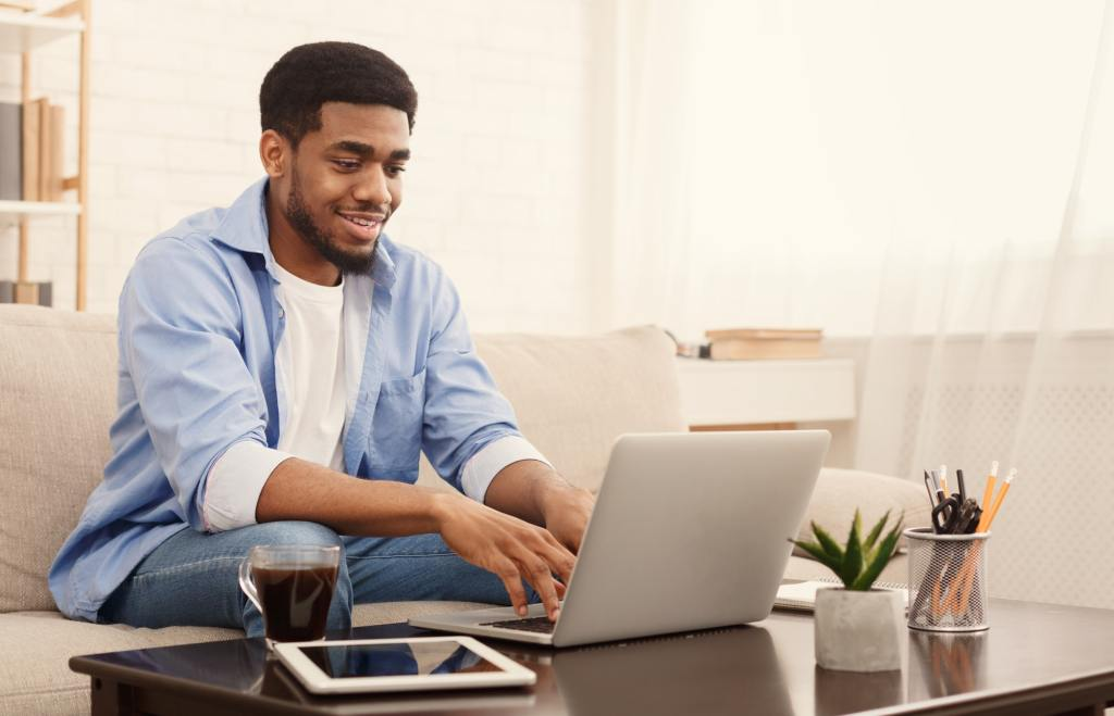 Millennial black man working on laptop in home office