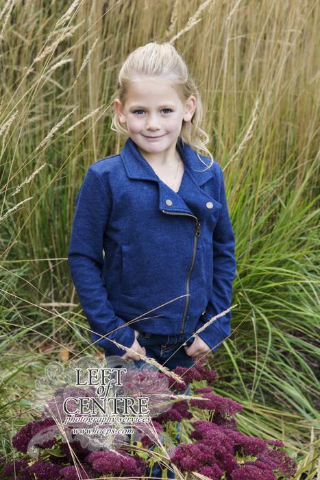 little girl standing in tall grass