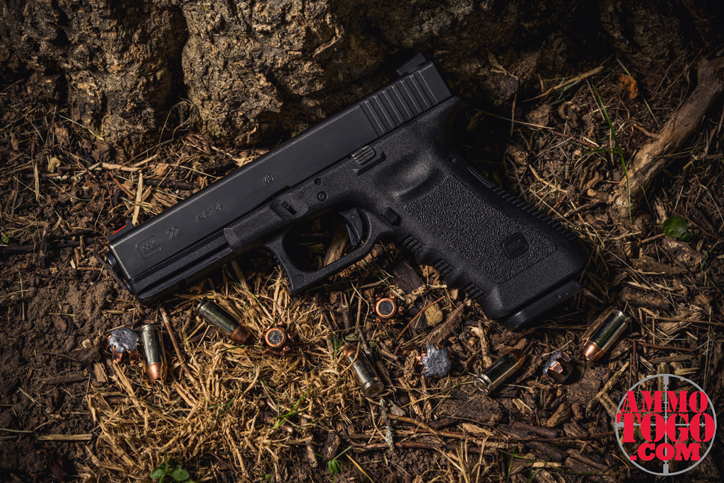 photo of a glock 22 pistol with JHP ammo outside