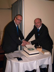 Worshipful Master, Michael Willetts cutting the cake with  the Worshipful Master of our Mother Lodge, W.Bro. Phil Wills