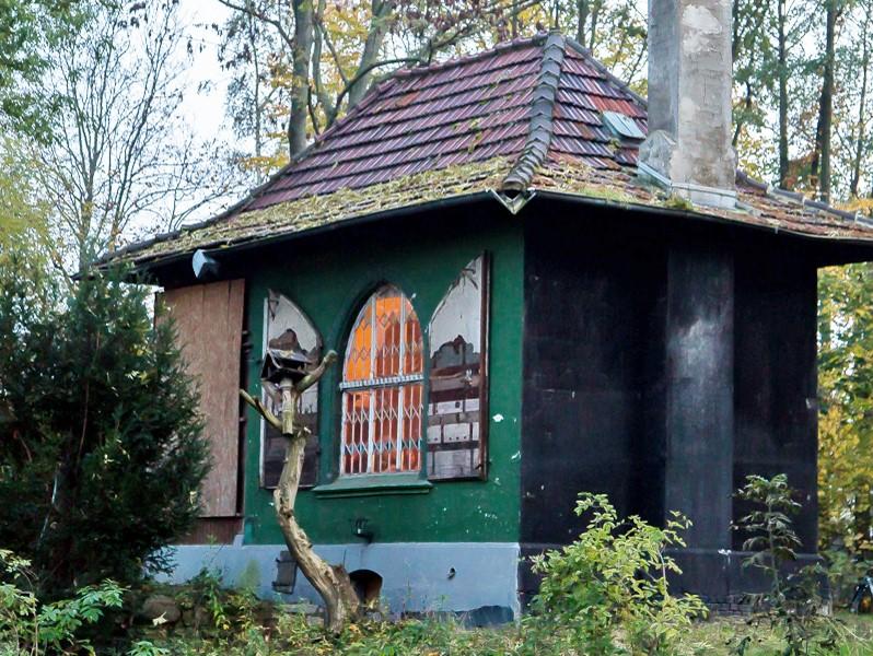 Das Kontorhaus am Jödebrunnen: Ein altes Gebäude mit grünem Anstrich, der an einigen Stellen abgeplatzt ist. Das Gebäude steht inmitten des Waldes. Aus dem einzigen Fenster mit Gitterstäben dringt Licht.