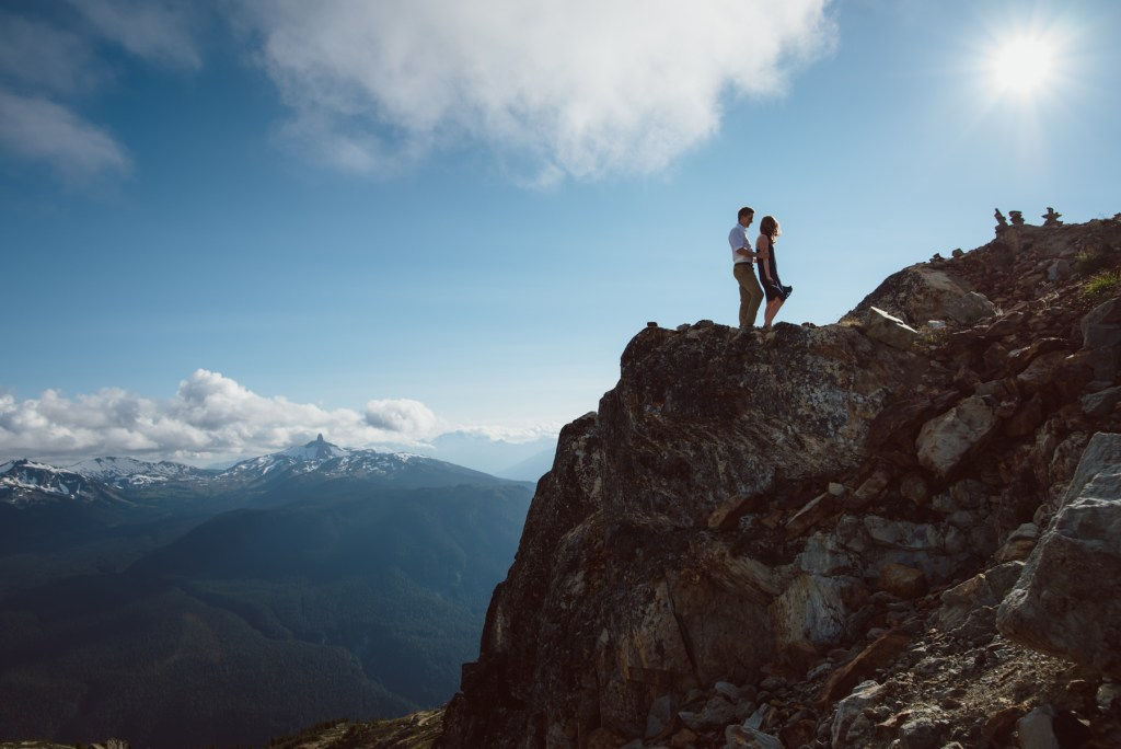 A couple standing on Whistler peak with black tusk in the distance
